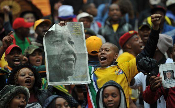 Ciudadanos sudafricanos congregados por el acto fúnebre para Nelson Mandela. / ALEXANDER JOE (AFP)