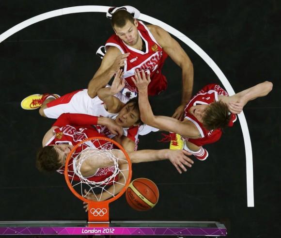 El chino Yi Li (en el centro) es bloqueado por los jugadores de Rusia durante el partido de baloncesto de la fase preliminar del Grupo B. Foto: MIKE SEGAR (REUTERS)
